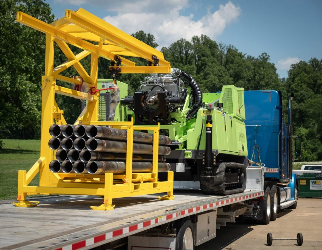 TUG pipe handling for sonic drill rig for transport